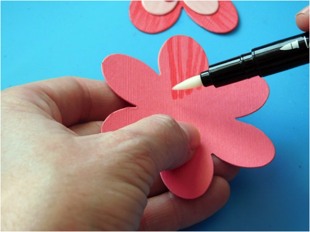 Terre Fry creates a tone on tone effect effortlessly by coloring in lines on a die cut flower with VersaMarker.