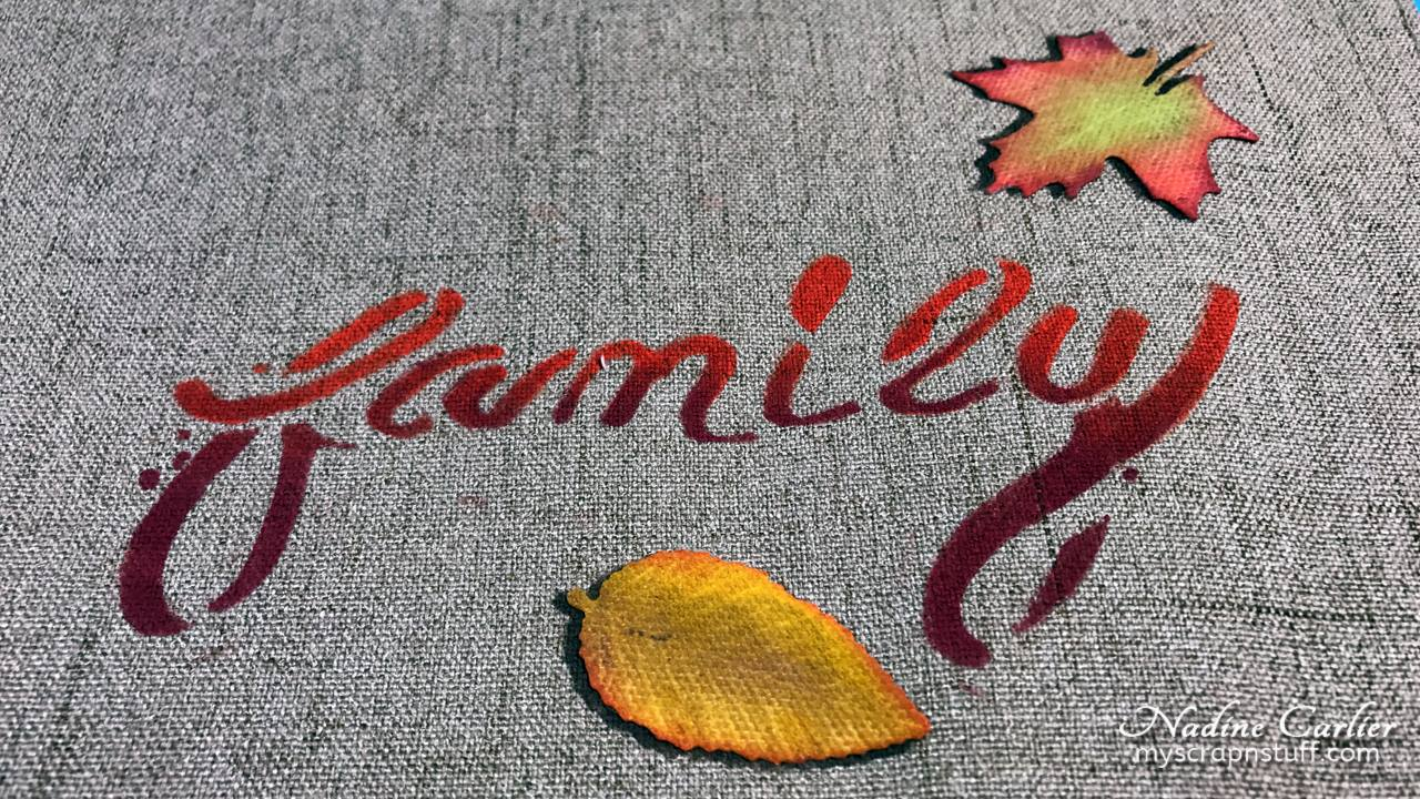 "Memento Luxe ink blanded into an ombre word ""family"" and autumn colored leaves on a canvas placement by Nadine Carlier."