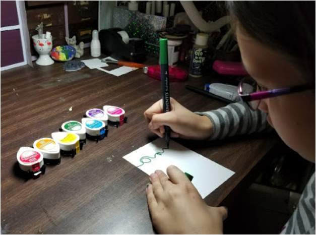 A girl draws a squiggly green line across a piece of white cardstock to represent a string for Christmas lights.