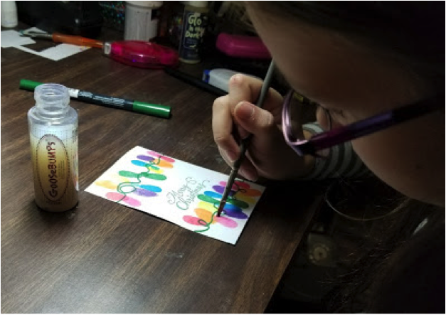 A girl applies GooseBumps texture medium to her handmade card featuring a string of Christmas lights.