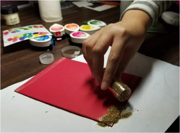 A child applies glitter to a taped area of cardstock in the process of making her handmade Christmas card.