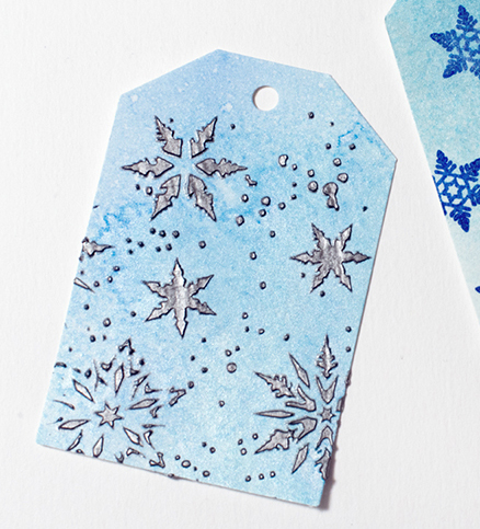 Elina Stromberg shows an example of Silver Creative Medium applied through a stencil on a snowflake themed tag.
