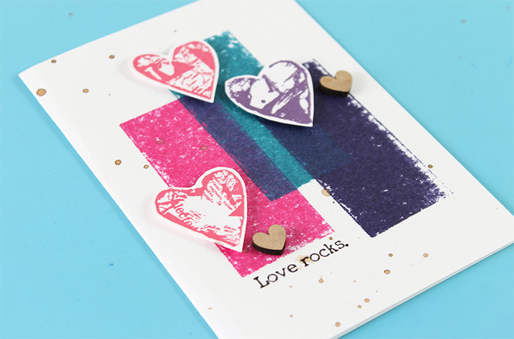 Adhere heart images to card panel with dimensional adhesive and add embellishments as needed in step 4 of a Valentine's Day card tutorial