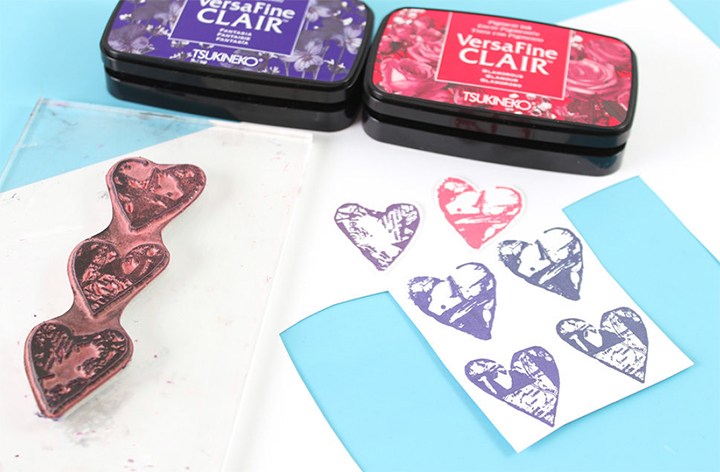 Use VersaFine Clair inkpads to ink heart stamps and stamp on white carstock. Fussy cut out heart images for step 3 of this Valentine's Day card tutorial.