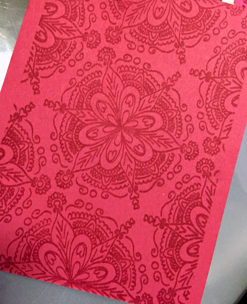 A red piece of cardstock has been stamped with an image in VersaMark ink to create a tone on tone effect.