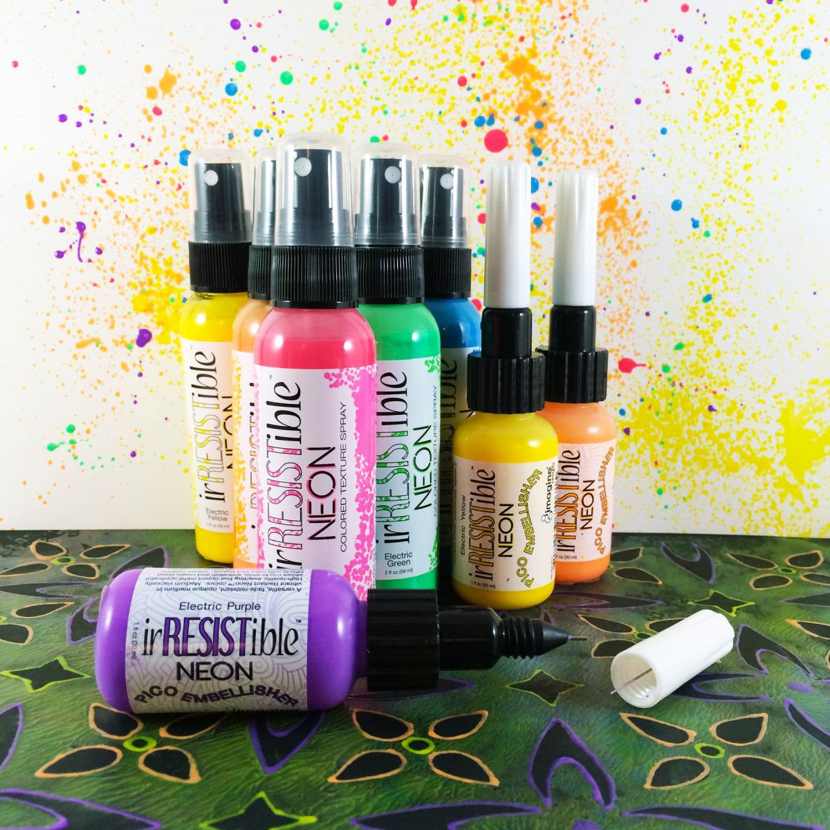 Multiple bottles of irRESISTible spray bottles and Pico Embellishers with a colorful background created using he product.