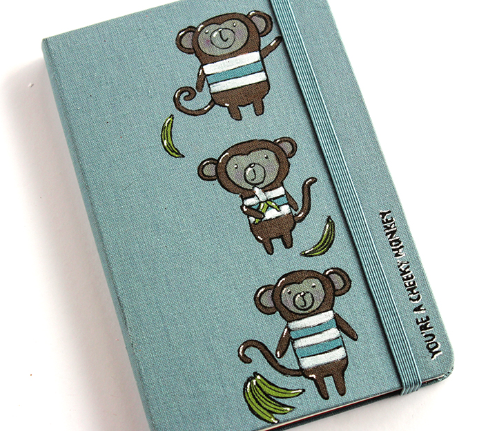 A moleskin notebook personalized with monkey images by stamping and coloring in with Tsukineko, Imagine and Gel Pen inks.