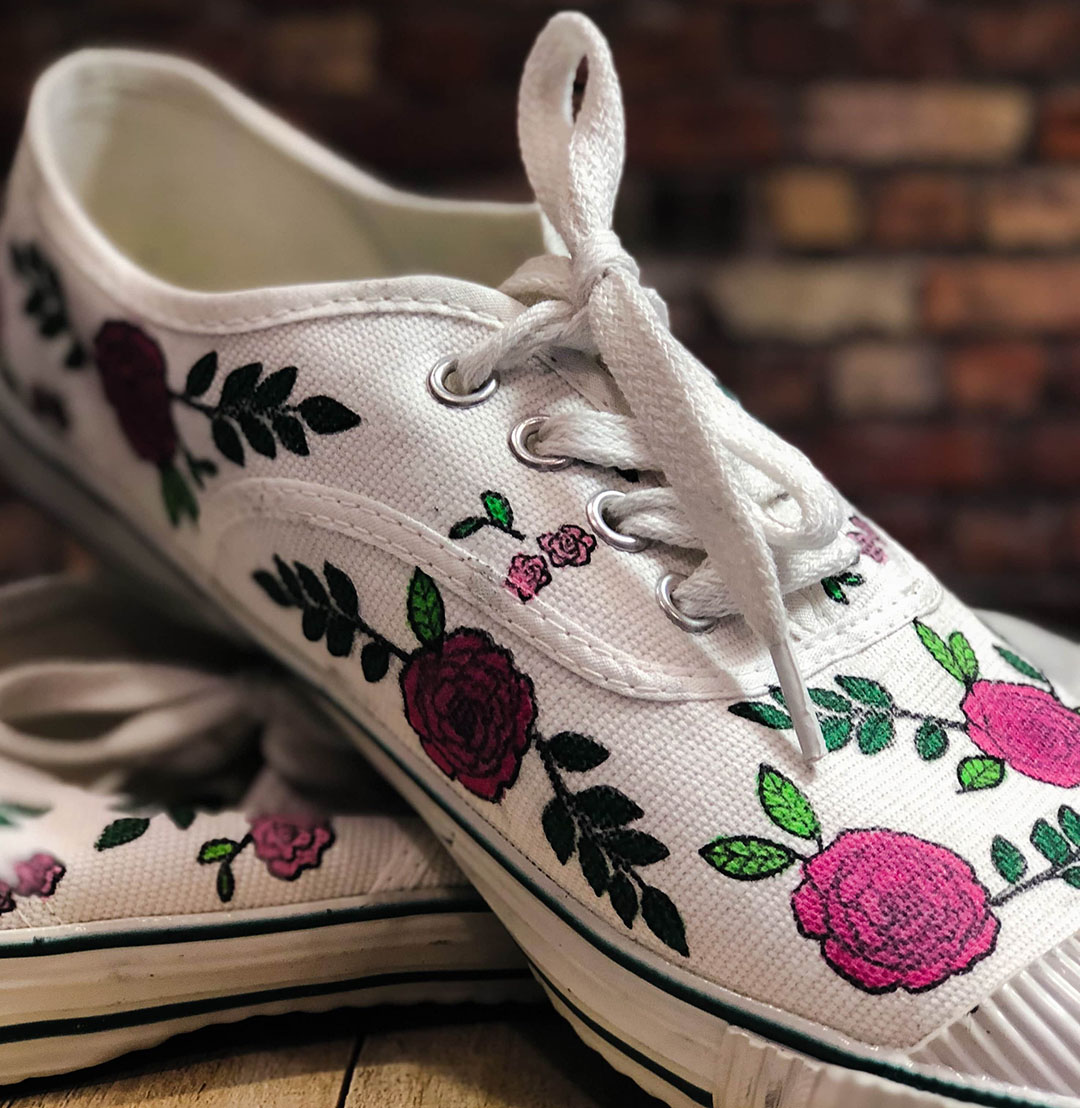 A self adorned pair of canvas shoes in a floral pattern and pink colors