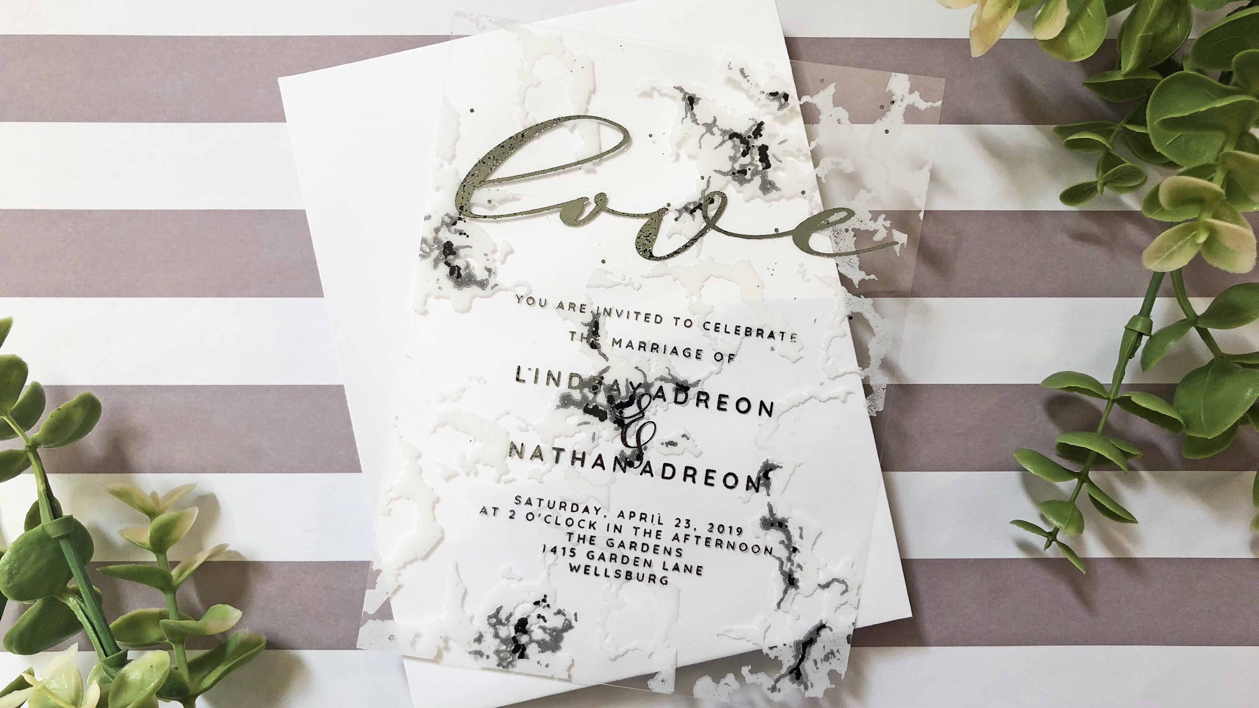 DIY clear wedding invitations with a marble pattern.