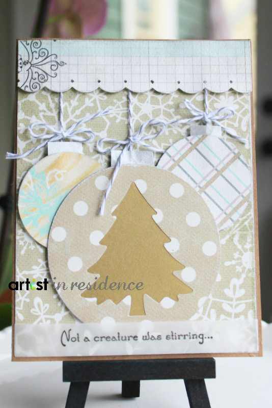 Handmade christmas card with cut out images of round christmas ornaments and the sentiment