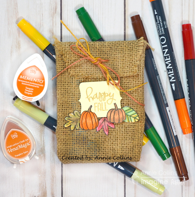 In this crafting lesson, Annie shows you a quick and easy Halloween Trick or Treat candy bag made with burlap material, pumpkin stamps, and Memento dye inks.